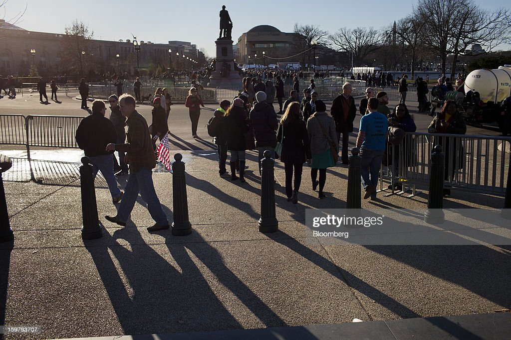 Pedestrians walk in front of the Capitol building ahead of the presidential inauguration in Washington, D.C., U.S., on Sunday, Jan. 20, 2013. As he enters his second term U.S. President Barack Obama has shed the aura of a hopeful consensus builder determined to break partisan gridlock and adopted a more confrontational stance with Republicans. Photographer: Victor J. Blue/Bloomberg via Getty Images