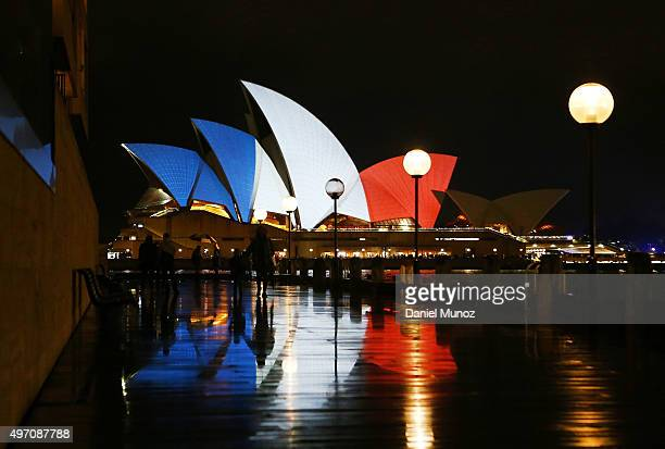 Pedestrians walk in front of the Sydney Opera House as its sails are illuminated in the colours of the French flag on November 14 2015 in Sydney...