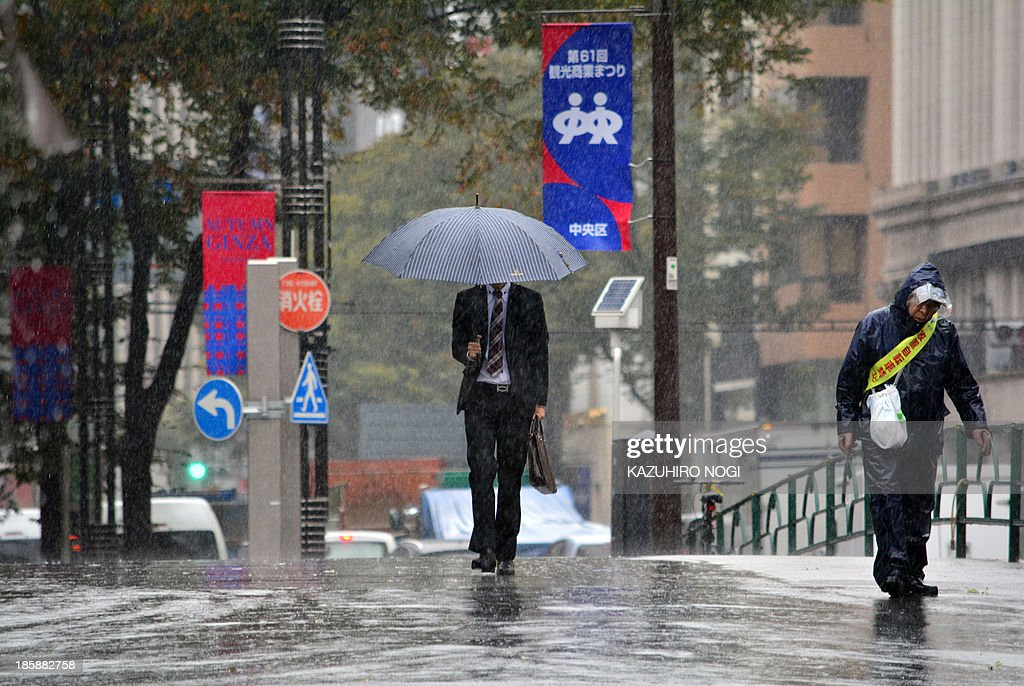 Pedestrians walk in heavy rain in Tokyo on October 26, 2013. People on a storm-battered island in Japan took shelter October 25, as another typhoon -- one of two looming in the Pacific -- looked set to sideswipe the coast. AFP PHOTO / KAZUHIRO NOGI