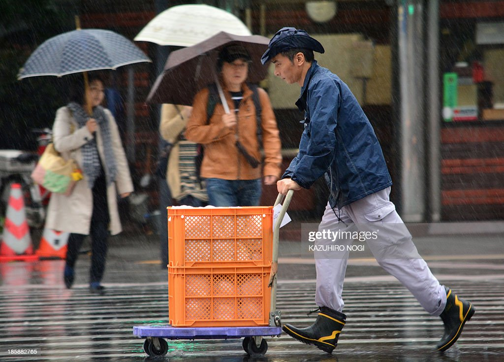 Pedestrians walk in heavy rain in Tokyo on October 26, 2013. People on a storm-battered island in Japan took shelter October 25, as another typhoon -- one of two looming in the Pacific -- looked set to sideswipe the coast.