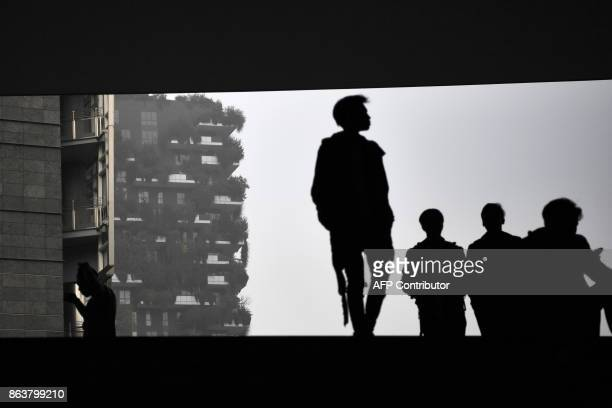Pedestrians walk in Piazza Gae Aulenti in the business district in Milan on October 20 as smog has reached alarming levels in northern Italy in...