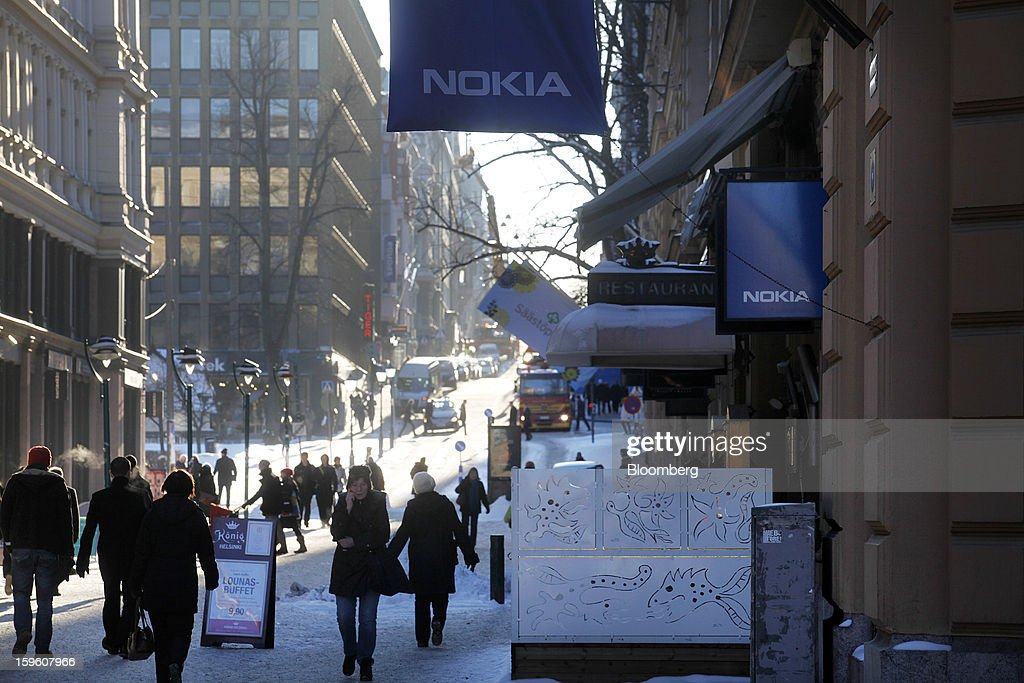 Pedestrians walk in snow past a Nokia Oyj store in Helsinki, Finland, on Thursday, Jan. 17, 2013. The pace of Finland's debt growth is alarming and the country must undertake economic reforms together with reining in spending, Finnish Prime Minister Jyrki Katainen said in an op-ed piece published in newspaper Savon Sanomat. Photographer: Ville Mannikko/Bloomberg via Getty Images