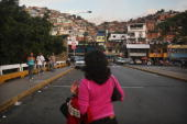 Pedestrians walk in the barrio of Petare after opposition supporters defeated a referendum on changes to the Constitution proposed by Venezuelan...