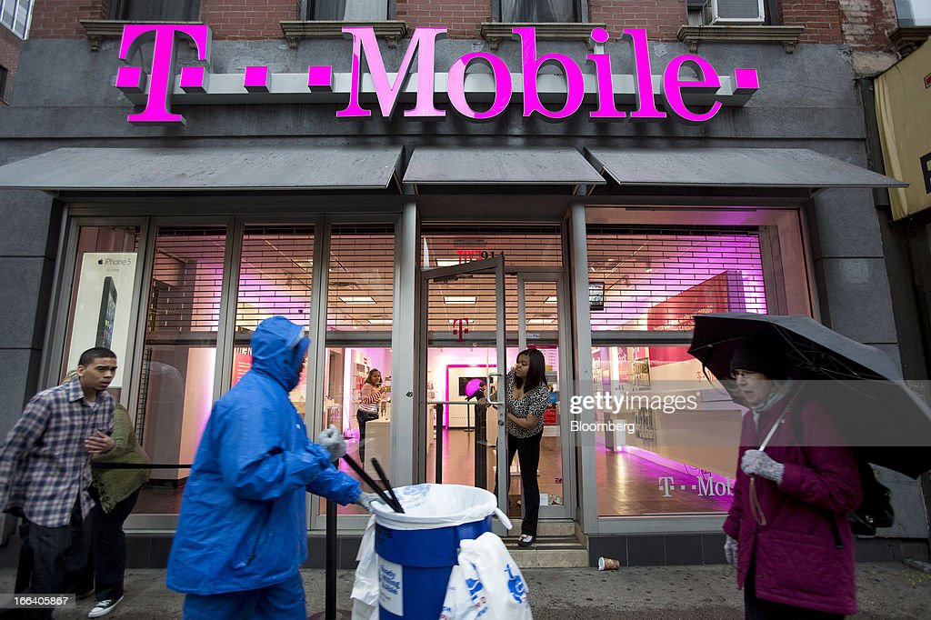 Pedestrians walk in the rain as T-Mobile USA Inc. employees prepare to open a retail location in New York, U.S., on Friday, April 12, 2013. T-Mobile USA Inc., the fourth-largest U.S. wireless carrier, will begin offering Apple Inc.'s iPhone for the first time today, providing the biggest showcase yet for its new installment-plan approach to selling phones. Photographer: Scott Eells/Bloomberg via Getty Images