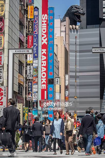 Pedestrians walk in the street under a 12 meter tall Godzilla replica head built on the 8th floor terrace of the Hotel Gracery Shinjuku on April 15...