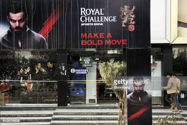 Pedestrians walk near advertising featuring Indian cricket captain Virat Kohli for Royal Challenge whiskey produced by United Spirits Ltd a distiller...