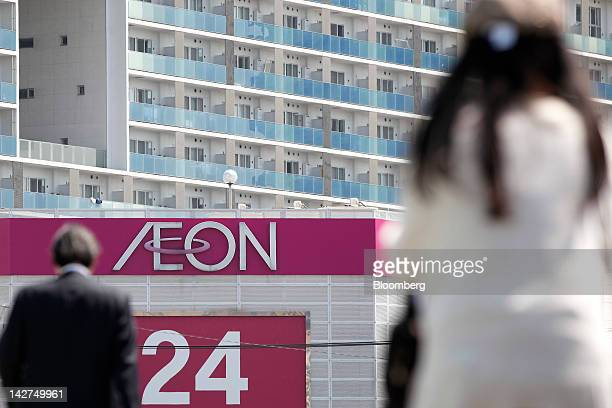 Pedestrians walk near an Aeon Co shopping center in Tokyo Japan on Thursday April 12 2012 Aeon Co Japan's largest supermarket operator reported...