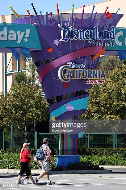 Pedestrians walk near the entrance to Disneyland and California Adventure theme parks on February 19 2009 in Anaheim California With the worsening...