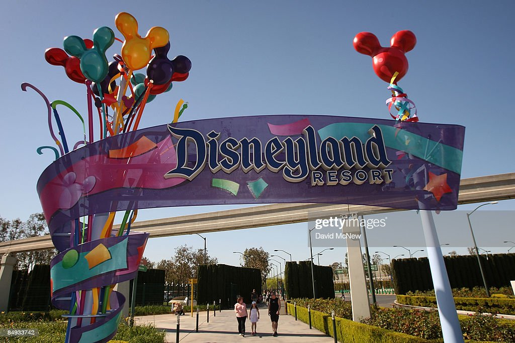 Pedestrians walk near the entrance to Disneyland Resort on February 19 2009 in Anaheim California With the worsening economy declining attendance and...