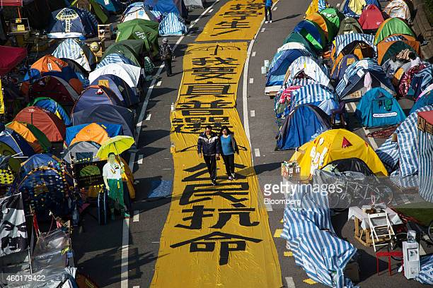 Pedestrians walk on a banner placed on the ground next to tents on Connaught Road Central outside the Central Government Offices in the Admiralty...