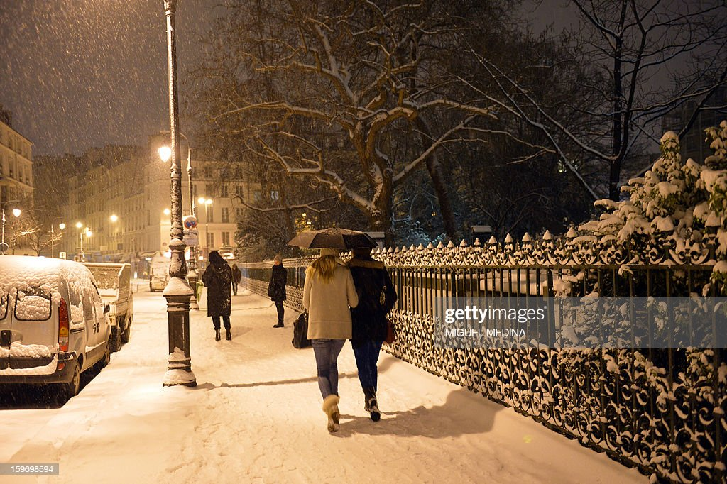 Pedestrians walk on a snow-covered street on January 18, 2013 in Paris.