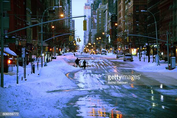 Pedestrians walk on Amsterdam Avenue early Sunday morning on January 24 2016 in New York City Most of New York's streets were cleaned up overnight...