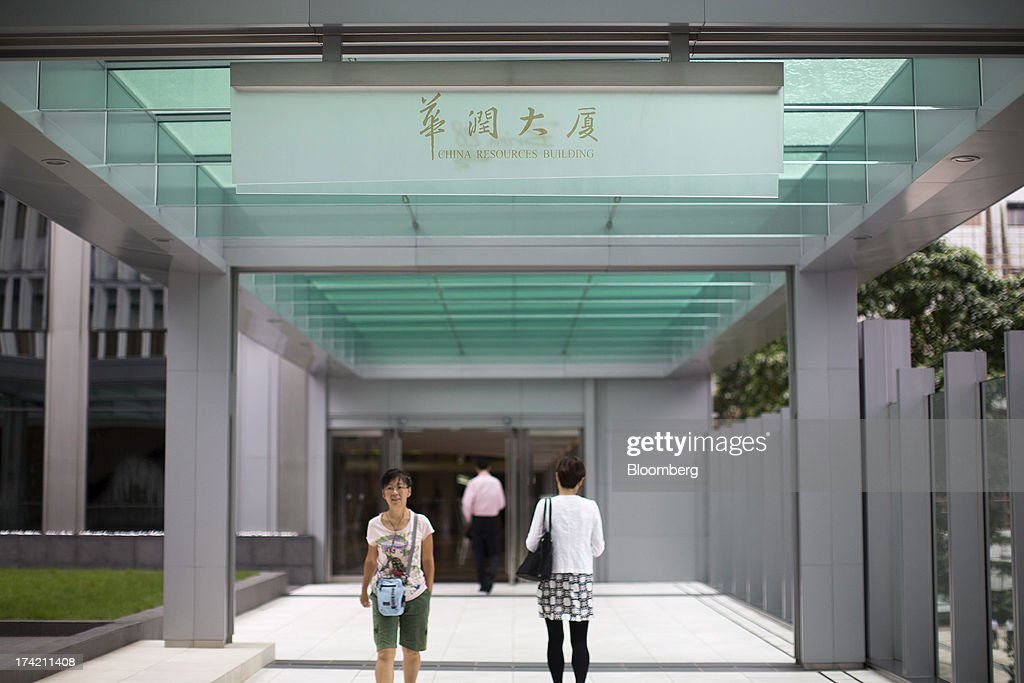 Pedestrians walk on an overpass leading to the China Resources Building, which houses the headquarters of China Resources Holdings Co., in Hong Kong, China, on Monday, July 22, 2013. State-run China Resources Holdings's plan to combine two units did not survive a shareholder vote today, after the value of the $7.1 billion offer plunged following an accusation that the parent's chairman deliberately overpaid for coal mines in 2010. Photographer: Jerome Favre/Bloomberg via Getty Images