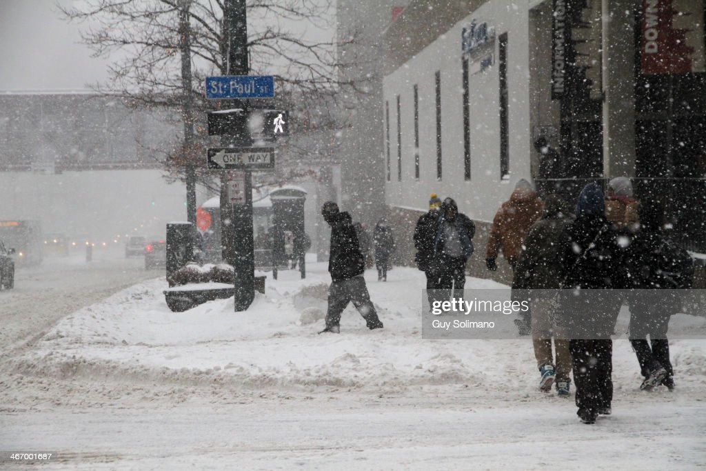 Pedestrians walk on Main Street during a snow storm on February 5, 2014 in Rochester, New York. An additional foot of snow blanketed Western New York overnight in the latest winter storm system that has affected areas from Kansas to Maine.