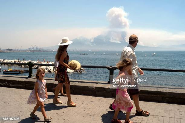 TOPSHOT Pedestrians walk on Naples Promenade as smoke rises from fires on the slopes of the volcano of Mount Vesuvius east of Naples on July 12 2017...