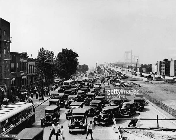 Pedestrians walk on the sidewalk and cross in front of cars exiting the Triborough Bridge in Harlem New York New York 1936