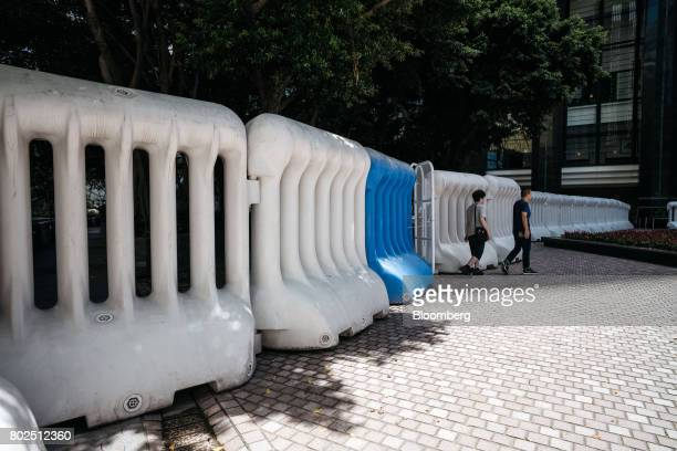 Pedestrians walk out of a gate between water barricades near the Hong Kong Convention and Exhibition Center ahead of Chinese President Xi Jinping's...