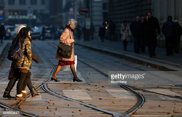 Pedestrians walk over tram lines as they cross a cobbled street in Cordusio square in Milan Italy on Tuesday Dec 10 2013 Italy's oneyear borrowing...