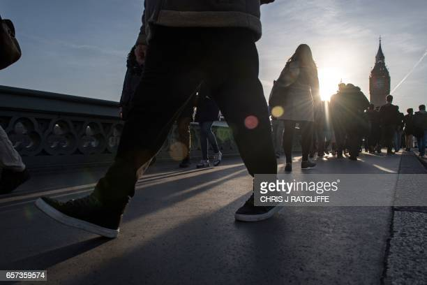 Pedestrians walk over Westminster Bridge in central London on March 24 2017 two days after the March 22 terror attack on the British parliament and...