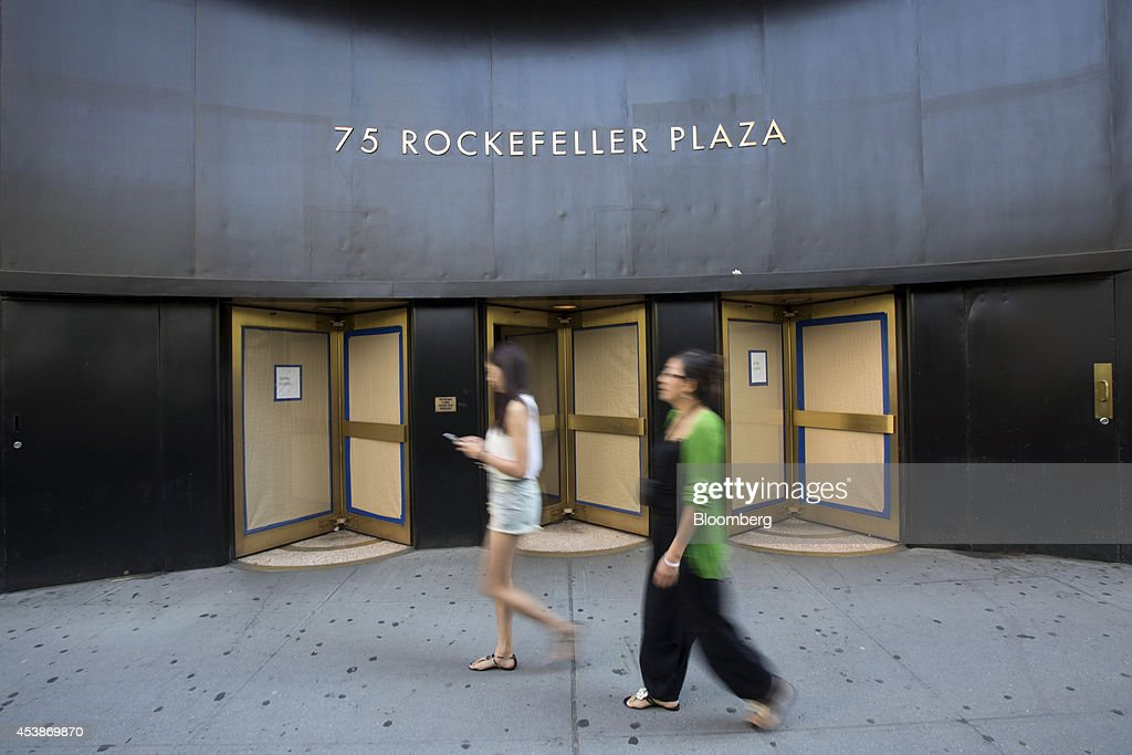 Pedestrians walk past 75 Rockefeller Plaza in New York, U.S., on Monday, Aug. 18, 2014. New landlord RXR Realty Corp. is upgrading the entire 630,000 square feet. The $150 million project includes raising office ceilings from 7.5 feet (2.3 meters) to 9 feet, and relocating mechanical equipment from the top floor to create new high-priced space, said Scott Rechler, RXRís chief executive officer. Photographer: Jin Lee/Bloomberg via Getty Images