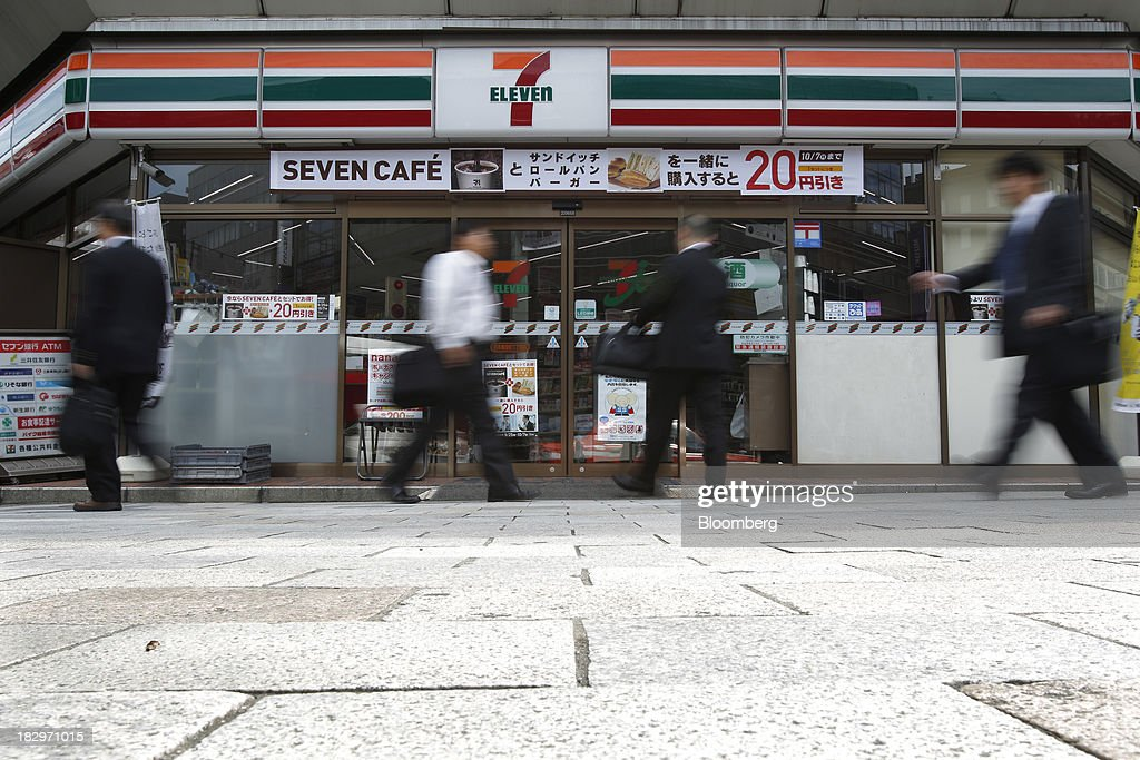 Pedestrians walk past a 7-Eleven convenience store, operated by Seven & I Holdings Co., in Tokyo, Japan, on Thursday, Oct. 3, 2013. Seven & I reported a 25 percent rise in first-half net income, in line with analysts' estimates. Photographer: Kiyoshi Ota/Bloomberg via Getty Images