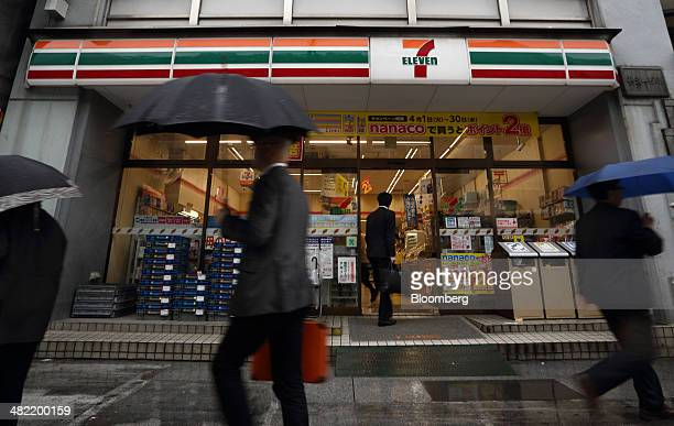Pedestrians walk past a 7Eleven convenience store operated by Seven I Holdings Co in Tokyo Japan on Thursday April 3 2014 Seven I forecasted a 47...
