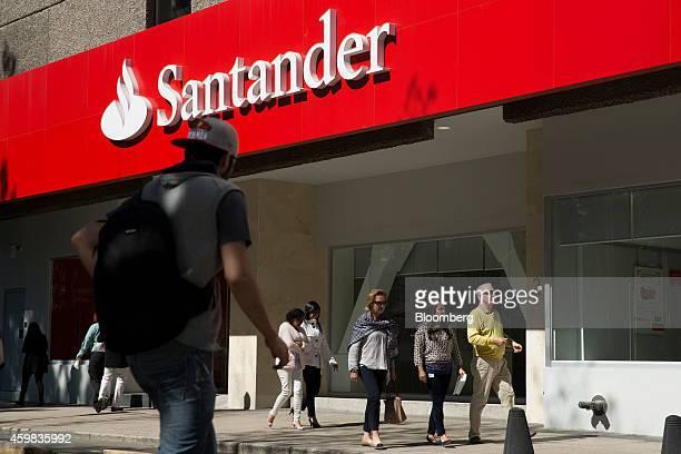 Pedestrians walk past a Banco Santander SA bank branch in Mexico City Mexico on Thursday Nov 27 2014 Santander Mexico announced last week that they...