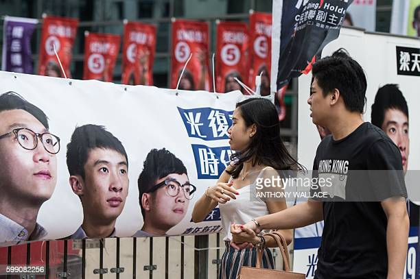 Pedestrians walk past a banner for new party Youngspiration showing disqualified candidate Edward Leung and Baggio Leung during the Legislative...