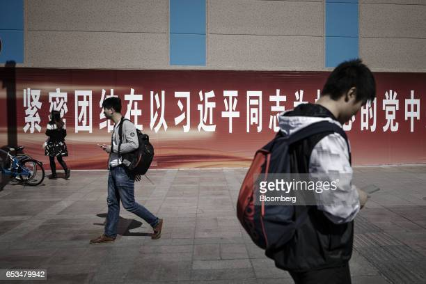 Pedestrians walk past a banner with text calling for citizens to unite around the Chinese Communist Party with president Xi Jinping at its core in...