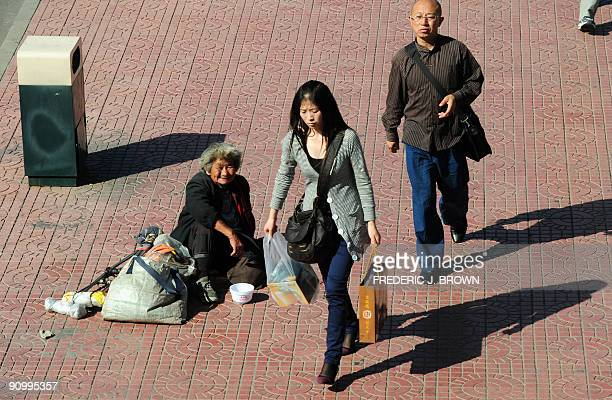 Pedestrians walk past a beggar and her belongings on a street in Beijing on September 21 2009 China approaches the October 1 60th anniversary of...