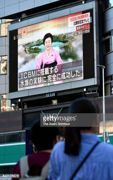 Pedestrians walk past a big monitor reporting North Korea's nuclear teston September 3 2017 in Tokyo Japan South Korea Japan and the US detected an...