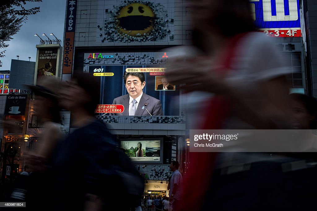 Pedestrians walk past a big screen showing a live broadcast of Japanese Prime Minister,Shinzo Abe as he delivers his WWII Anniversary Statement on August 14, 2015 in Tokyo, Japan. Japanese Prime Minister Abe delivered a war anniversary statement ahead of the anniversary of Japan's defeat in the second world war. The statement included such keywords as 'apology from the heart,' 'colonial rule,' and 'aggression.'
