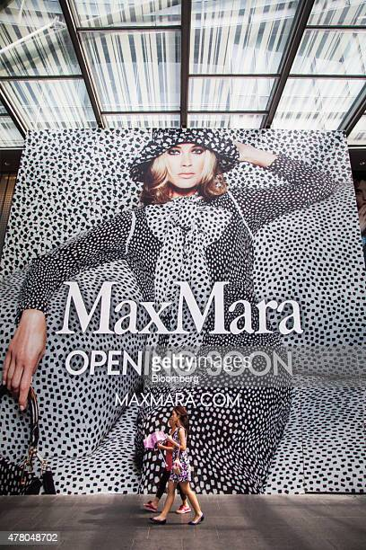 Pedestrians walk past a billboard advertising the opening of a Max Mara Fashion Group Srl store on Orchard Road in Singapore on Sunday June 21 2015...