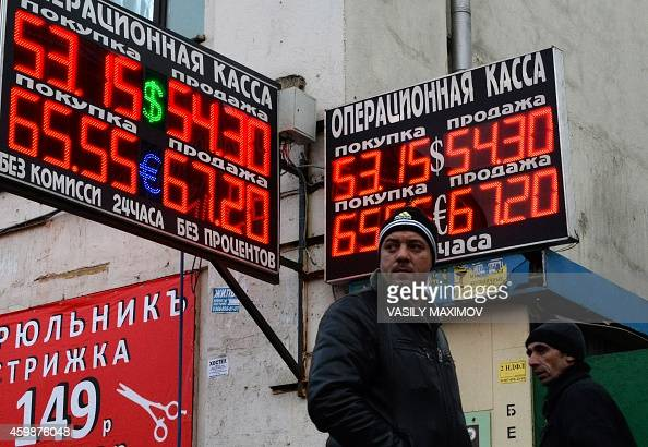 Pedestrians walk past a board listing foreign currency rates against the Russian ruble outside an exchange office in Moscow on December 3 2014 The...