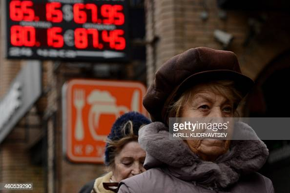 Pedestrians walk past a board listing foreign currency rates against the Russian ruble outside an exchange office in central Moscow on December 16...