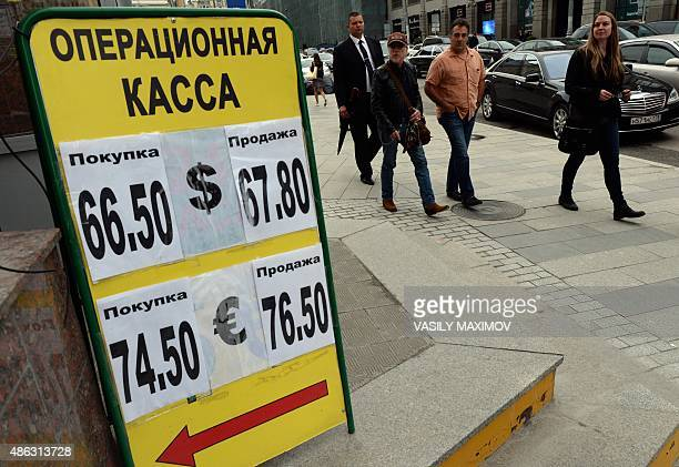 Pedestrians walk past a board listing foreign currency rates against the Russian ruble outside an exchange office in Moscow on September 3 2015 AFP...
