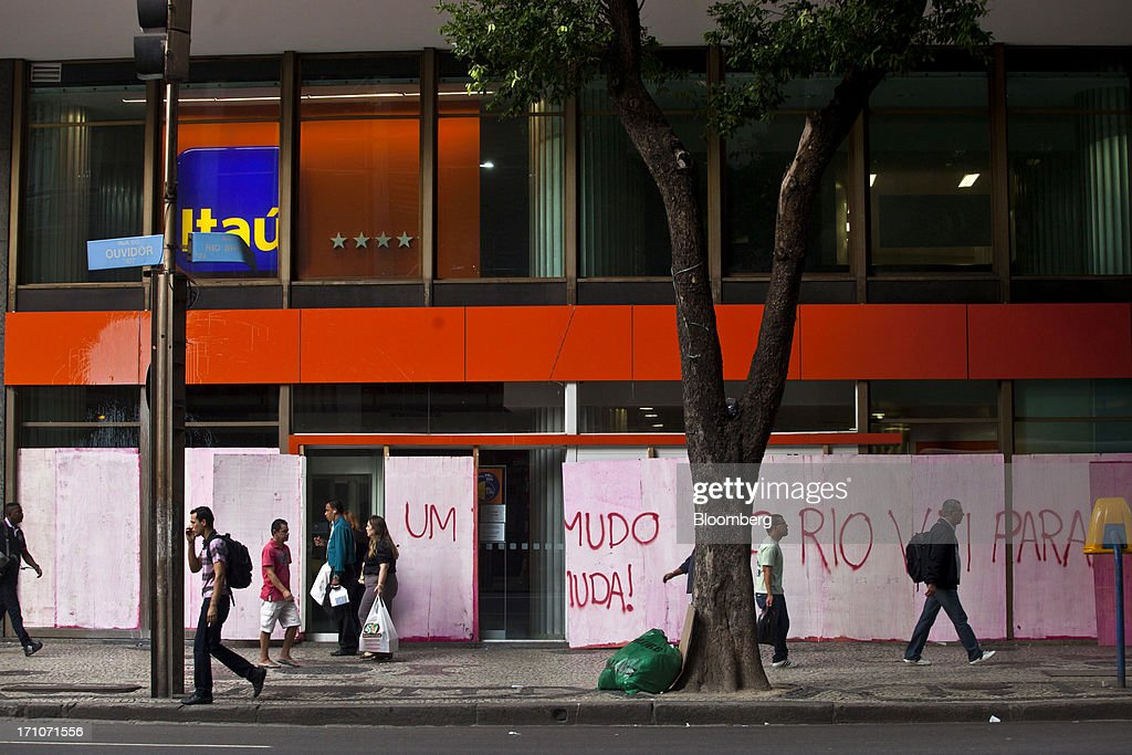 Pedestrians walk past a boarded up Itau Unibanco Holding SA branch in Rio de Janeiro, Brazil, on Friday, June 21, 2013. Brazils swelling street rebellion claimed its second fatality in the largest and most violent protests yet, as 1 million demonstrators rallied for better public services and an end to corruption. Photographer: Dado Galdieri/Bloomberg via Getty Images