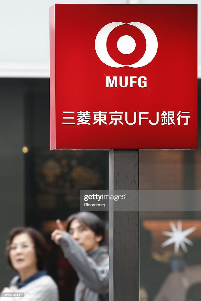 Pedestrians walk past a branch of Bank of Tokyo Mitsubishi UFJ Ltd. in Tokyo, Japan, on Tuesday, Nov. 13, 2012. Mitsubishi UFJ Financial Group Inc. (MUFG) is scheduled to announce first-half earnings results on Nov. 14. Photographer: Kiyoshi Ota/Bloomberg via Getty Images