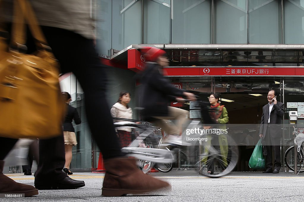 Pedestrians walk past a branch of Bank of Tokyo Mitsubishi UFJ Ltd. in Tokyo, Japan, on Tuesday, Nov. 13, 2012. Mitsubishi UFJ Financial Group Inc. is scheduled to announce first-half earnings results on Nov. 14. Photographer: Kiyoshi Ota/Bloomberg via Getty Images