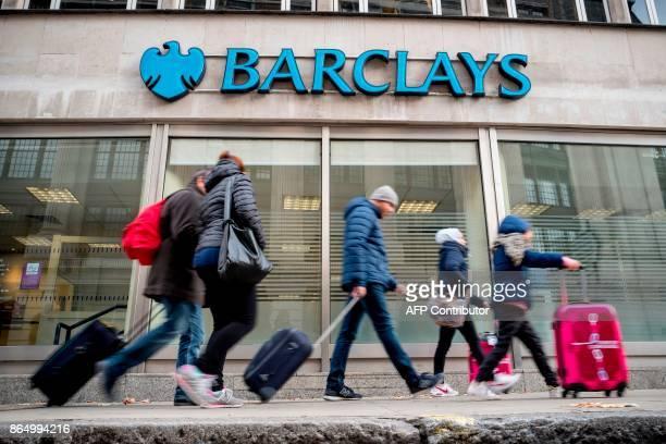 Pedestrians walk past a branch of Barclays bank in central London on October 22 2017 / AFP PHOTO / AFP PHOTO AND Tolga Akmen / Tolga Akmen