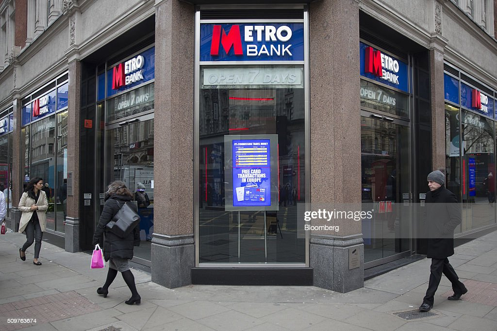 Pedestrians walk past a branch of Metro Bank Plc in London, U.K., on Friday, Feb. 12, 2016. Metro Bank, the British lender backed by wealthy American financiers including Steven Cohen, plans to sell shares to existing investors before going public on the London Stock Exchange. Photographer: Simon Dawson/Bloomberg via Getty Images
