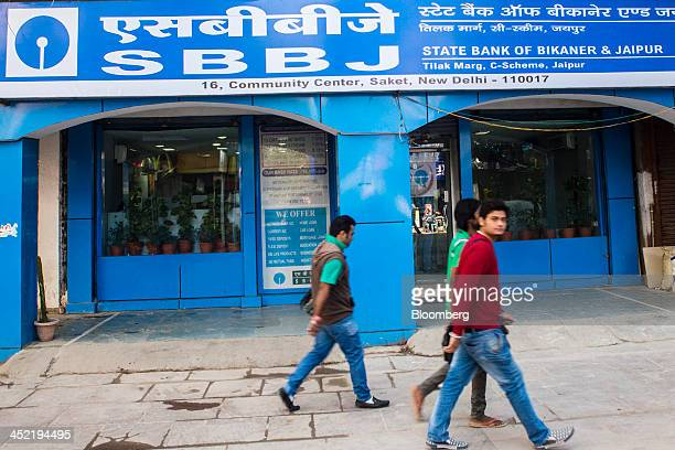 Pedestrians walk past a branch of State Bank of Bikaner Jaipur in the Saket area of New Delhi India on Tuesday Nov 26 2013 India is scheduled to...