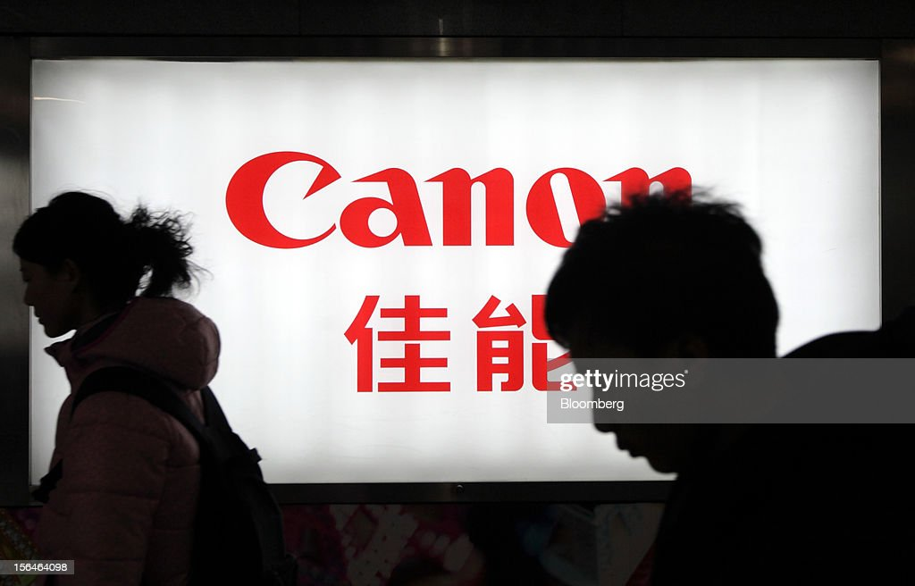 Pedestrians walk past a Canon Inc. advertisement in Beijing, China, on Thursday, Nov. 15, 2012. Canon is the world's largest camera maker. Photographer: Tomohiro Ohsumi/Bloomberg via Getty Images