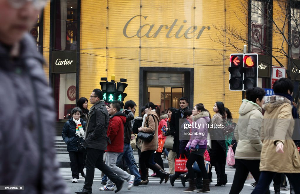 Pedestrians walk past a Cartier store, operated by Cie. Financiere Richemont SA, in Shanghai, China, on Wednesday, Feb. 6, 2013. China's economic growth accelerated for the first time in two years as government efforts to revive demand drove a rebound in industrial output, retail sales and the housing market. Photographer: Tomohiro Ohsumi/Bloomberg via Getty Images
