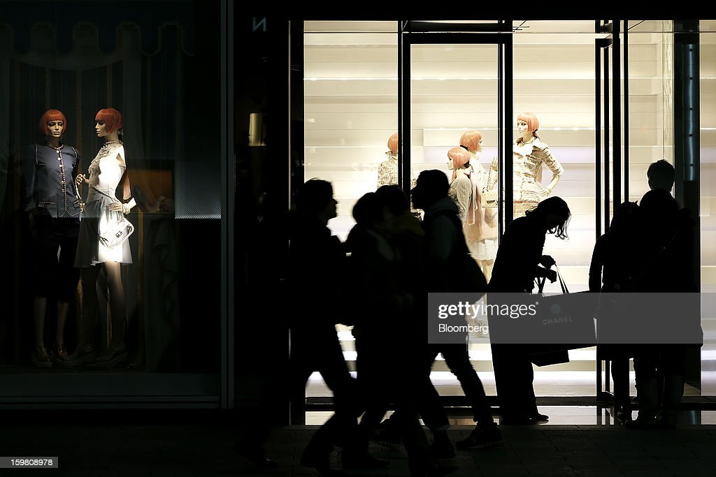 Pedestrians walk past a Chanel SA store as an employee, third right, hands bags to customers in the Ginza district of Tokyo, Japan, on Sunday, Jan. 20, 2013. Japan's consumer prices excluding fresh food, a benchmark monitored by the central bank, haven't advanced 2 percent for any year since 1997, when a national sales tax was increased. Photographer: Kiyoshi Ota/Bloomberg via Getty Images