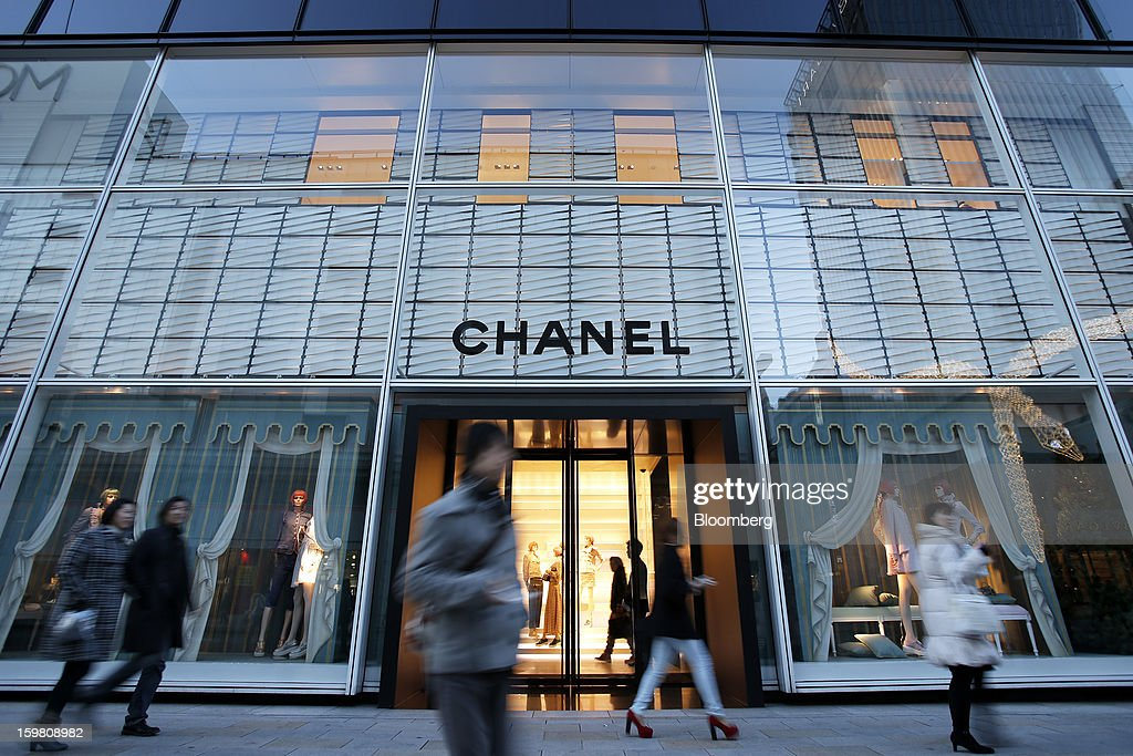Pedestrians walk past a Chanel SA store in the Ginza district of Tokyo, Japan, on Sunday, Jan. 20, 2013. Japan's consumer prices excluding fresh food, a benchmark monitored by the central bank, haven't advanced 2 percent for any year since 1997, when a national sales tax was increased. Photographer: Kiyoshi Ota/Bloomberg via Getty Images