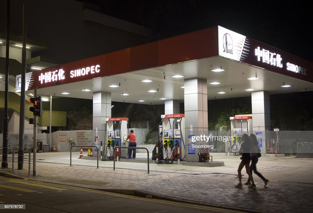 Pedestrians walk past a China Petroleum & Chemical Corp. (Sinopec) gas station at night in Hong Kong, China, on Tuesday, Aug. 22, 2017. Sinopec is scheduled to report second-quarter results on Aug. 25. Photographer: Vivek Prakash/Bloomberg via Getty Images