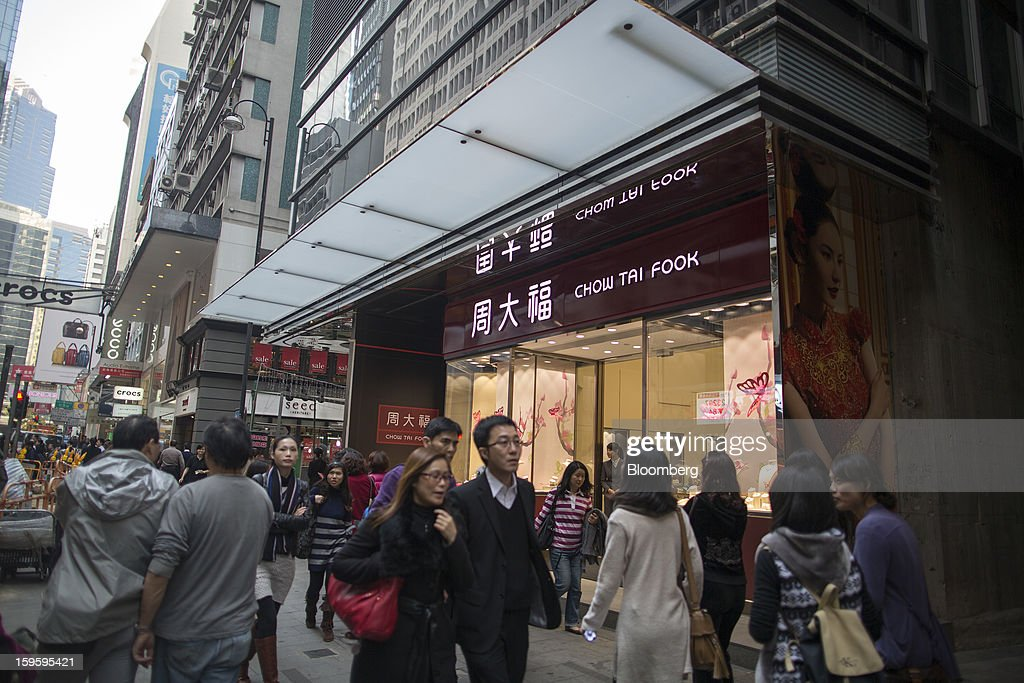 Pedestrians walk past a Chow Tai Fook Jewellery Group Ltd. store in the Central district of Hong Kong, China, on Wednesday, Jan. 16, 2013. Chow Tai Fook Jewellery, the world's biggest jeweler by market value, posted an 8 percent drop in third-quarter same-store sales as Chinese shoppers curbed spending amid a slower economy. Photographer: Jerome Favre/Bloomberg via Getty Images