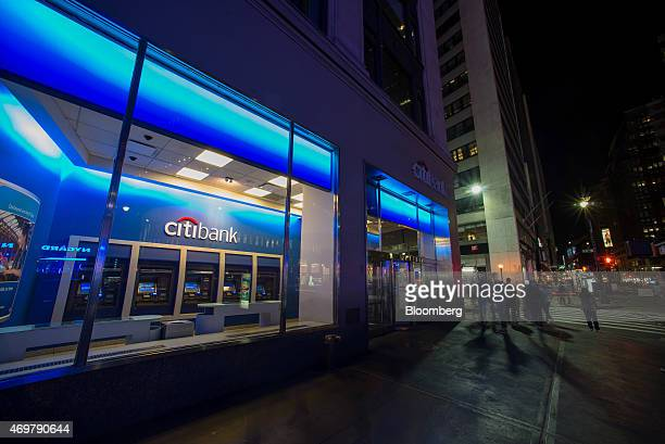 Pedestrians walk past a Citigroup Inc Citibank branch at night in New York US on Saturday April 11 2015 Citigroup Inc is scheduled to release...