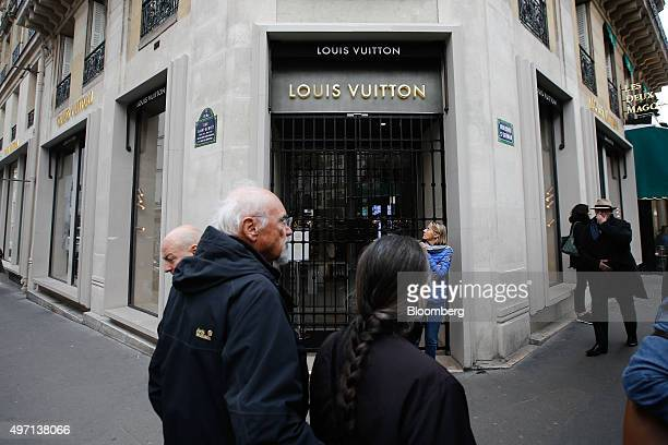 Pedestrians walk past a closed Louis Vuitton store operated by LVMH Moet Hennessy Louis Vuitton SA on the Champs Elysee in Paris France on Saturday...
